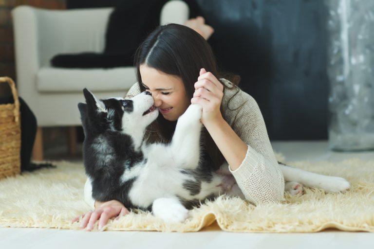 Frau-kuschelt-mit-Husky-Hund-auf-Teppich-768×512