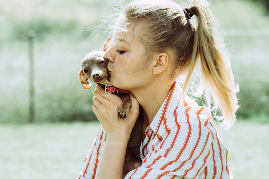 Tyttö pussaa koiranpentua
